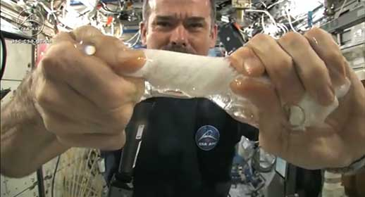 Wringing out a wet cloth in space